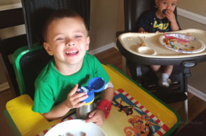 Brian using adaptive seating and a tray to enjoy a meal with his brother
